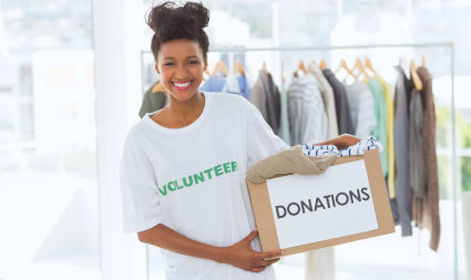 volunteer holding a box of donated clothes